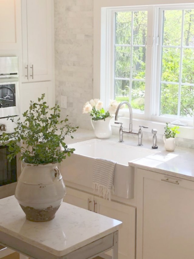 Serene tranquil white kitchen with farm sink, marble subway tile, Viatera Minuet quartz counters, white Shaker cabinets, and white oak flooring. Design and photo: Hello Lovely Studio. #kitchendesign #whitekitchen #minuet #whitequartz #benjaminmoorewhite