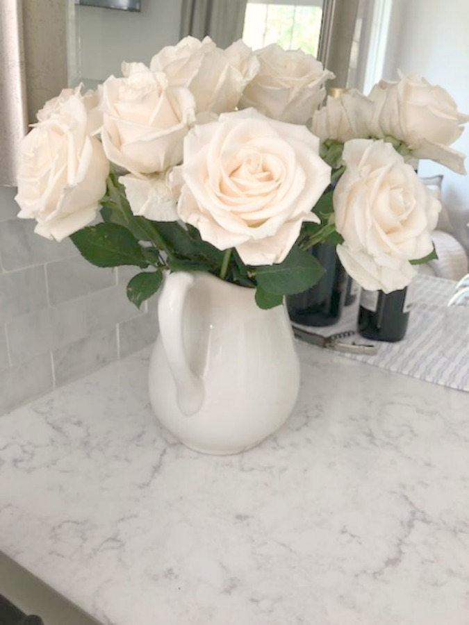 White glacier roses in vintage ironstone pitcher on Viatera Minuet quartz countertop in my kitchen - Hello Lovely Studio.