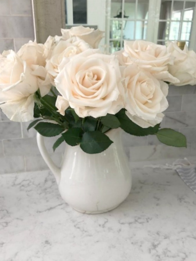 White glacier roses in ironstone pitcher on counter (Viatera Minuet quartz) - Hello Lovely Studio.