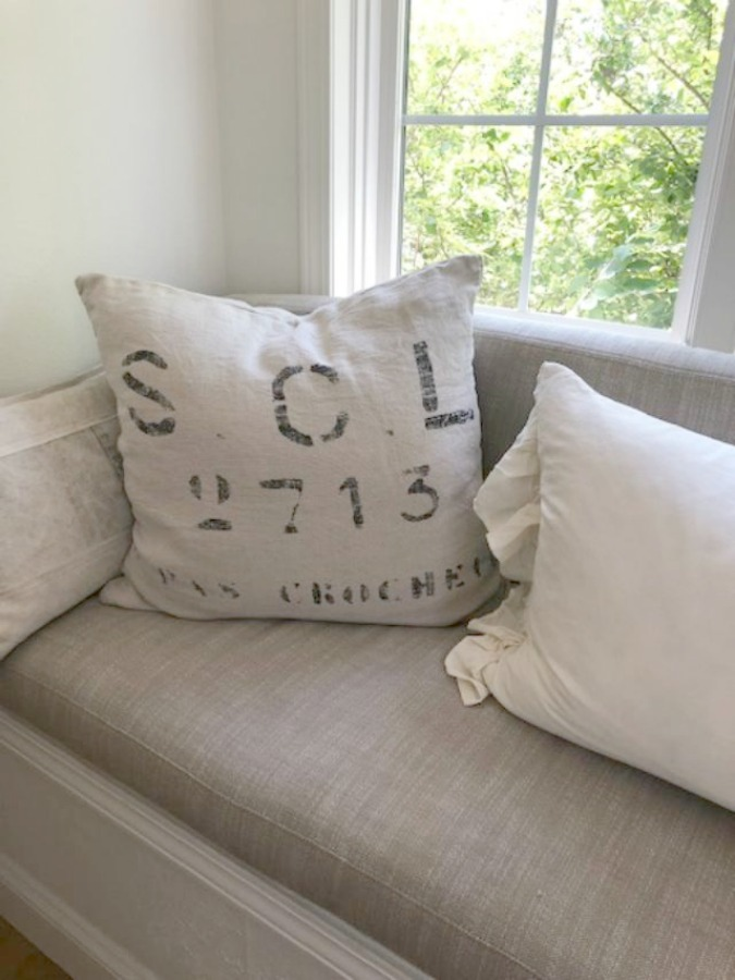 Detail of linen cushion window seat in my serene European inspired white kitchen - Hello Lovely Studio.