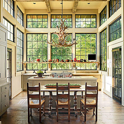 Magnificent kitchen in an Alabama lakehouse - rustic farm table is a humble moment in a grand room with soaring ceilings and stunning windows. Architecture: Jeffrey Dungan. Design: Richard Tubb. Photo: Chris Luker for Southern Living magazine.