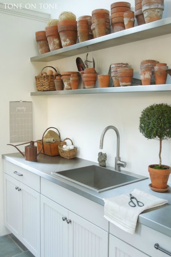 Potting shed gardening shed interior with shelves of terracotta pots, stainless sink, and topiaries - Tone on Tone Antiques. Come explore She Shed Chic, Potting Shed & Backyard Inspiration.