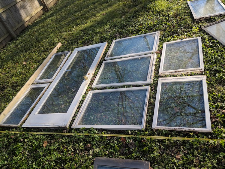 Vintage windows arranged on ground in preparation for a DIY greenhouse. Come explore She Shed Chic, Potting Shed & Backyard Inspiration.