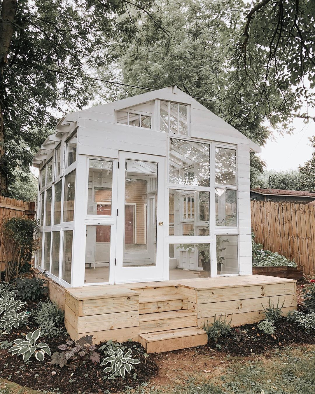 Backyard greenhouse made from vintage windows. Come explore She Shed Chic, Potting Shed & Backyard Inspiration.