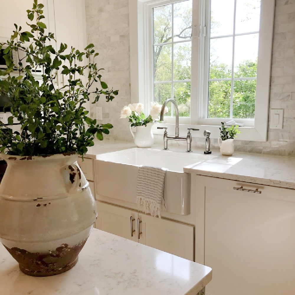 Hello Lovely's white European country modern French kitchen with Minuet Viatera quartz counters, farm sink, industrial cart, and marble subway backsplash.