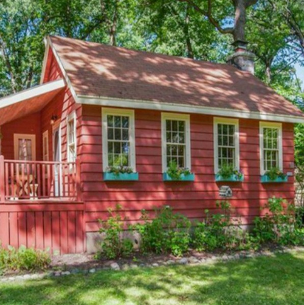 Charming red cottage near Lake Geneva with porches, rustic wood interiors, window boxes, and cheerful color palette.