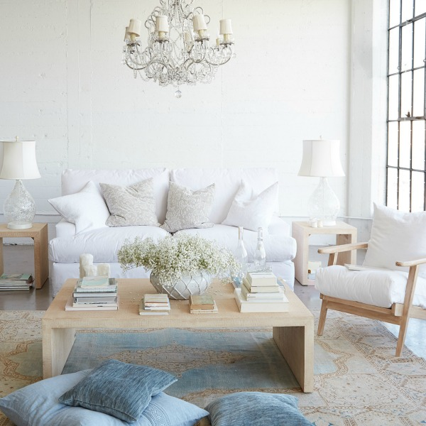 Shabby chic living room with crystal chandelier and blue accents designed by Rachel Ashwell.