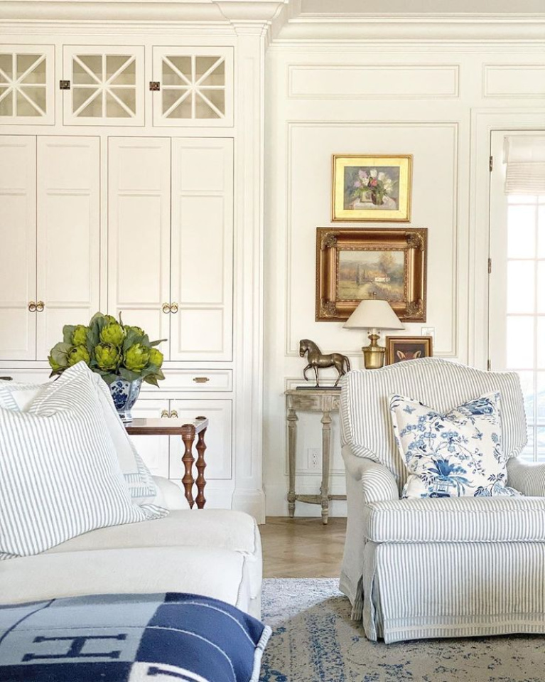 Blue accents in a gorgeous white keeping room near the kitchen by The Fox Group. #thefoxgroup #interiordesign #blueandwhite #keepingroom #livingrooms #traditionalstyle #classicdesign