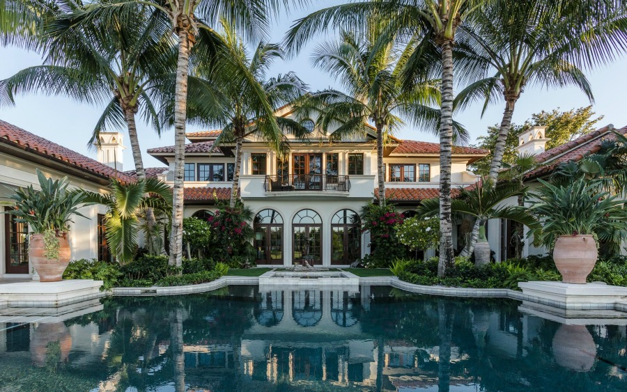 Luxurious and tropical home exterior with magnificent pool and design by Tom Stringer on Hello Lovely Studio.