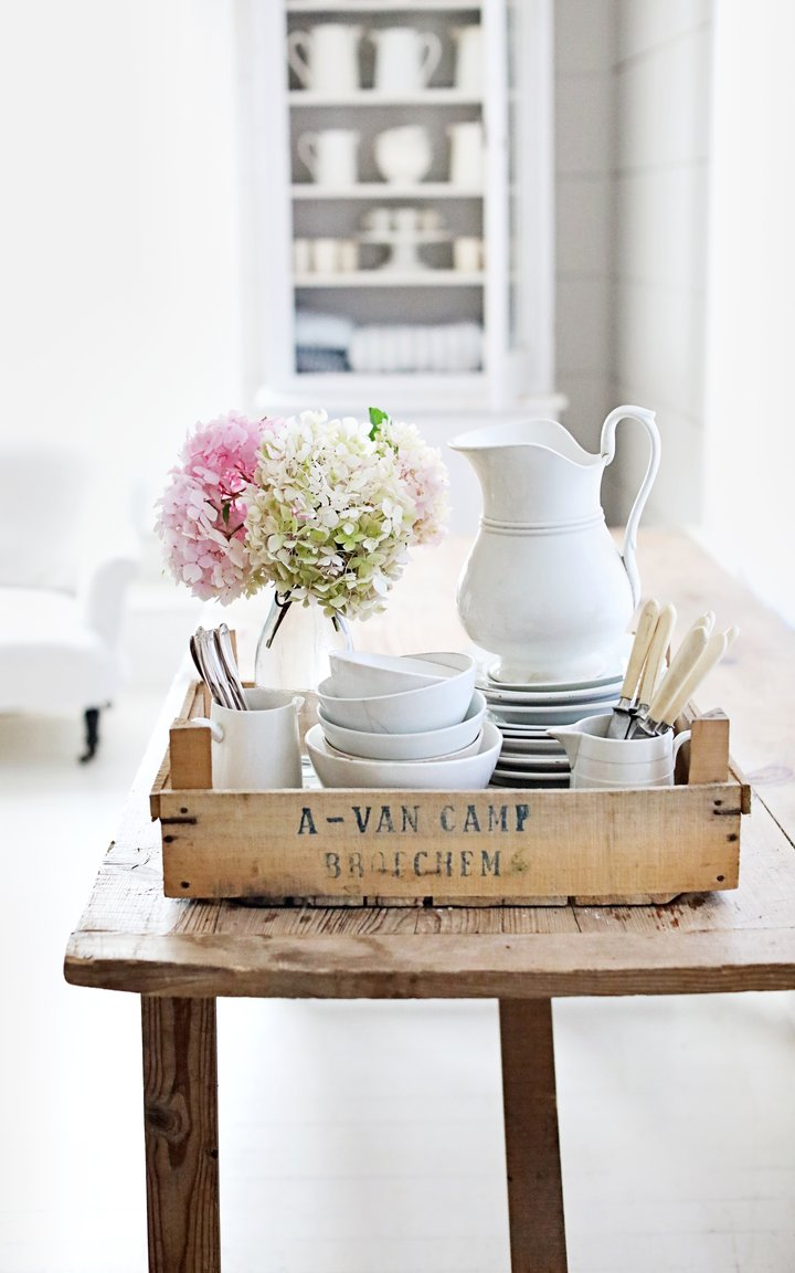 Rustic White French Farmhouse style vignette with Belgian crate, ironstone, and hydrangea upon a wood table. Dreamy Whites Atelier. #frenchfarmhouse #rusticdecor #frenchcountry