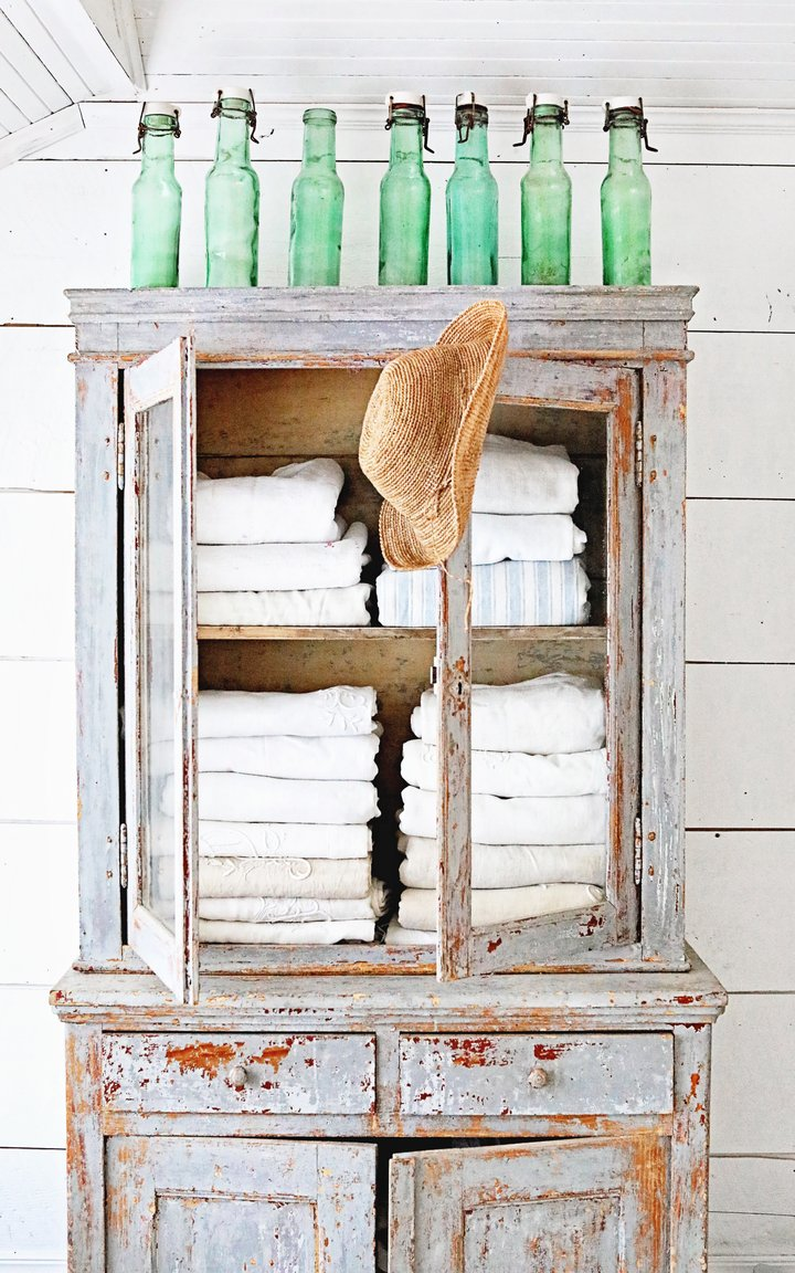 Weathered blue grey vintage wood cabinet with white towels inside. French canning jars decorate the top, and shiplap adorns the wall behind it. Dreamy Whites Atelier. #frenchfarmhouse #bluegry #shabbychic