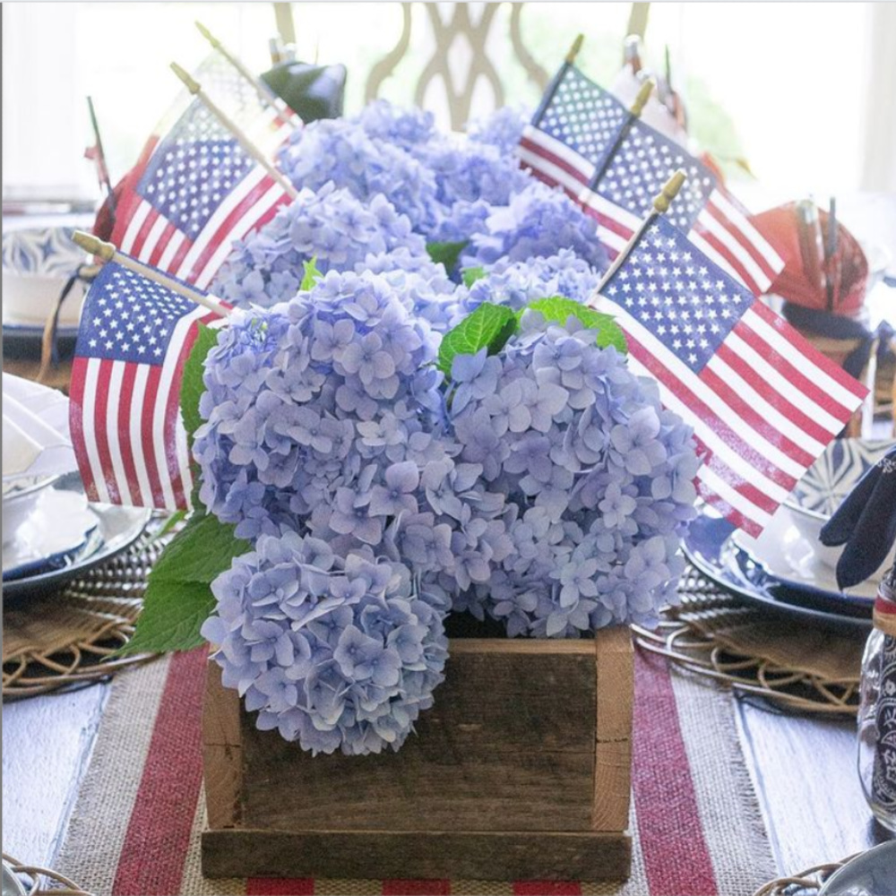 Blue hydrangea 4th of July centerpiece with American flags on table - @houseofelynryn. #centerpieces #tablescapes #july4 #hydrangea
