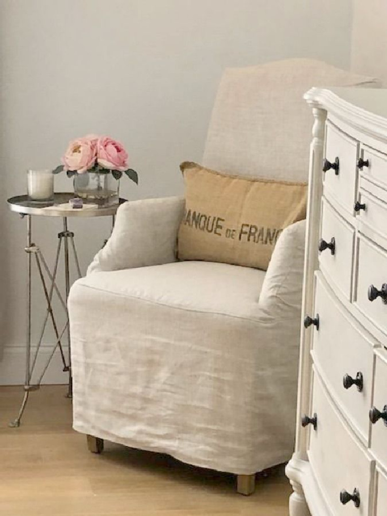 Benjamin Moore White on walls of Hello Lovely Studio's European country bedroom with Belgian linen slipcovered chair. #benjaminmoore #whitepaints #interiordesign #paintcolors