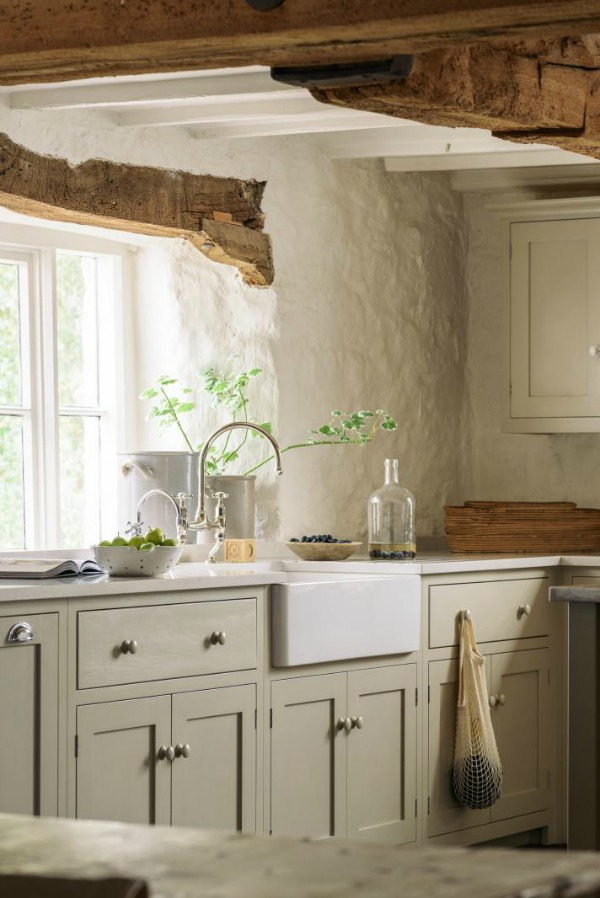 Beautifully rustic English country kitchen in the UK by deVOL has Shaker style cabinetry, farm sink, and a serene palette. #englishcountry #countrykitchen #kitchendesign #rustickitchen #frenchkitchen #shakerkitchen