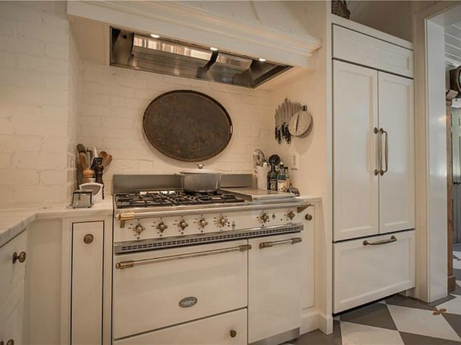 White Lacanche range in kitchen of an elegant historic home with Old World style and beautifully classic European inspired interiors in Marietta Georgia was built for the Kennedy-DuPre family. ee more of the Entry, Living Room & Kitchen Design Inspiration As Well As Photos of a Beautiful Georgia Tudor Exterior on Hello Lovely Studio.
