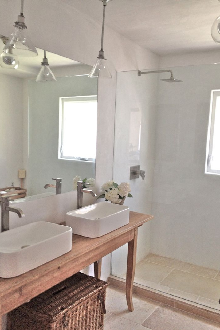 Charming custom bath by Giannetti Home with vessel sinks and pool plastered shower. #bathroomdesign #vesselsinks #europeancountry #frenchfarmhouse #rusticelegance