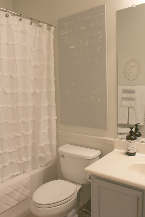 French script stenciled canvas in a serene bathroom by Hello Lovely Studio. Paint color on canvas is Behr Classic Silver and on walls is Valspar Salute. Click through for Perfect Light Gray Paint Colors You'll Love as Well as Interior Design Inspiration Photos. #bestgreypaint #paintcolors