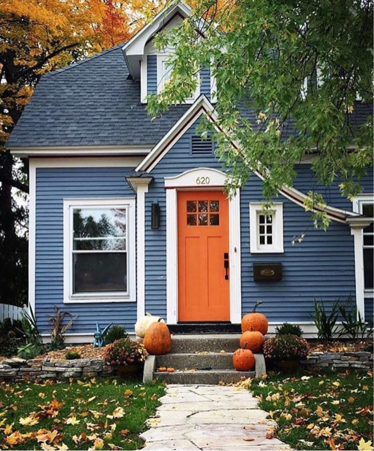 Indigo blue Tudor style house with bright orange door in fall with leaves and pumpkins - Bobby's Girl. #houseexteriors #bluehouse #indigoblue #navyblue #blueandorange #fallcurbappeal #frontfacade