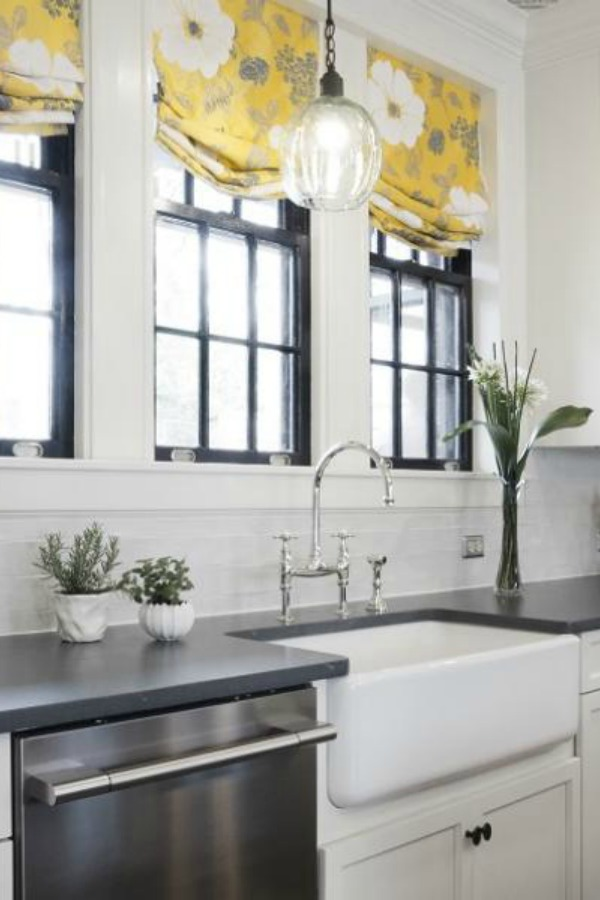 Beautiful renovated white classic kitchen with subway tile, farm sink, and yellow accents. Marsh Kitchens executed the lovely design which features black windows, warm wood floors, butcher block insert in huge island, and luxury range and hood.