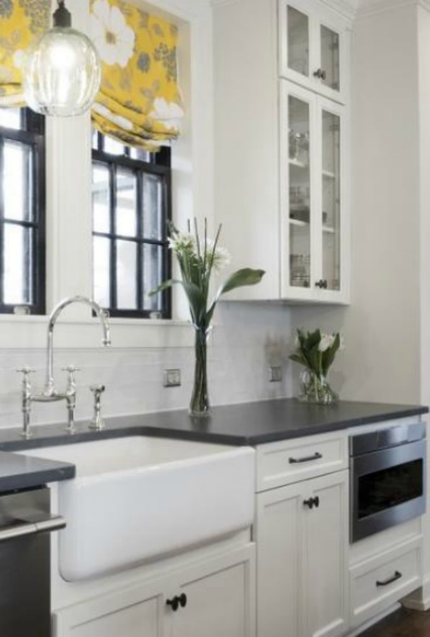 Beautiful renovated white classic kitchen in Julian Price Mansion with subway tile, farm sink, and yellow accents. Marsh Kitchens executed the lovely design which features black windows, warm wood floors, butcher block insert in huge island, and luxury range and hood.