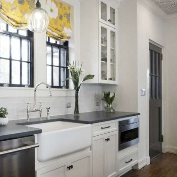 Beautiful design details in the renovated white classic Julian Price House kitchen with subway tile, farm sink, and yellow accents. Marsh Kitchen & Bath executed the lovely design which features black windows, warm wood floors, butcher block insert in huge island, and luxury range and hood.