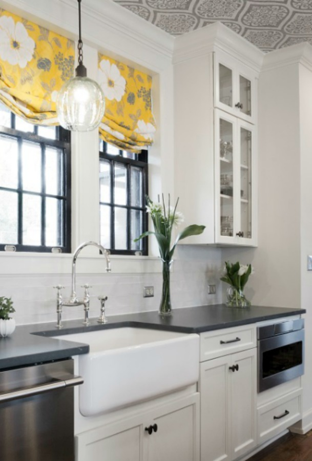 Beautiful design details in a renovated white classic kitchen with subway tile, farm sink, and yellow accents. Marsh Kitchen & Bath executed the lovely design which features black windows, warm wood floors, butcher block insert in huge island, and luxury range and hood.