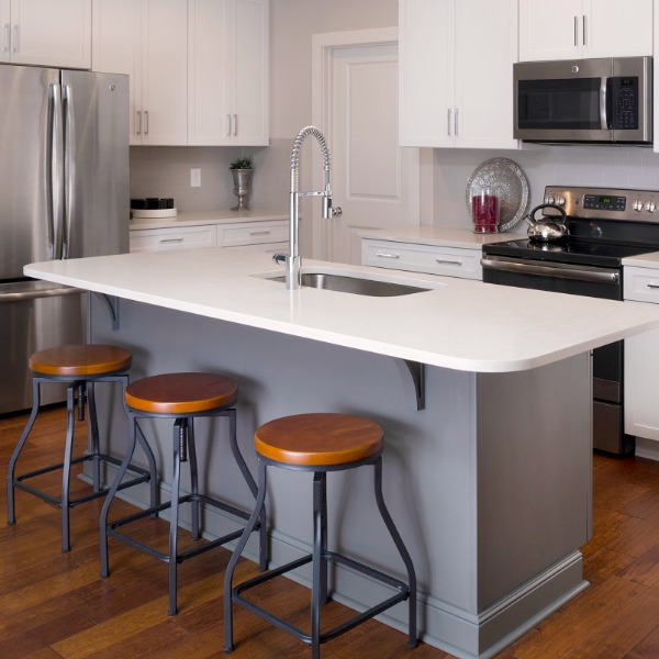 Simple kitchen design with grey island and white cabinets with stainless appliances - Marsh Kitchens.