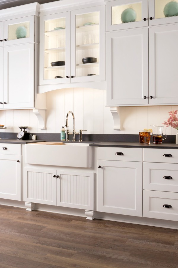 Beautiful kitchen design with white Shaker cabinets, apron front farm sink, and dark counters by Marsh Kitchens on Hello Lovely.