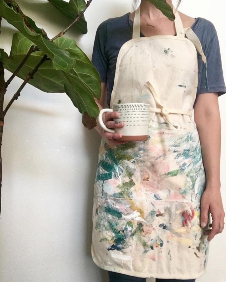 Artist Rebekah May in a painting smock.