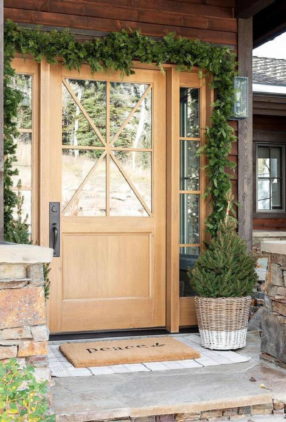 Gorgeous rustic wood front door, garland, peace door mat layered on plaid rug - McGee & Co.