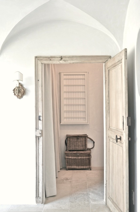 A vintage door opens to a lovely laundry room with rustic French farmhouse style and a wall mounted drying rack. Patina Farm by Giannetti Home.