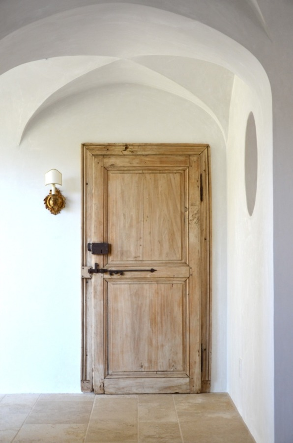 Old World style reclaimed wood door from Europe leads to the laundry room at Patina Farm by Giannetti Home.