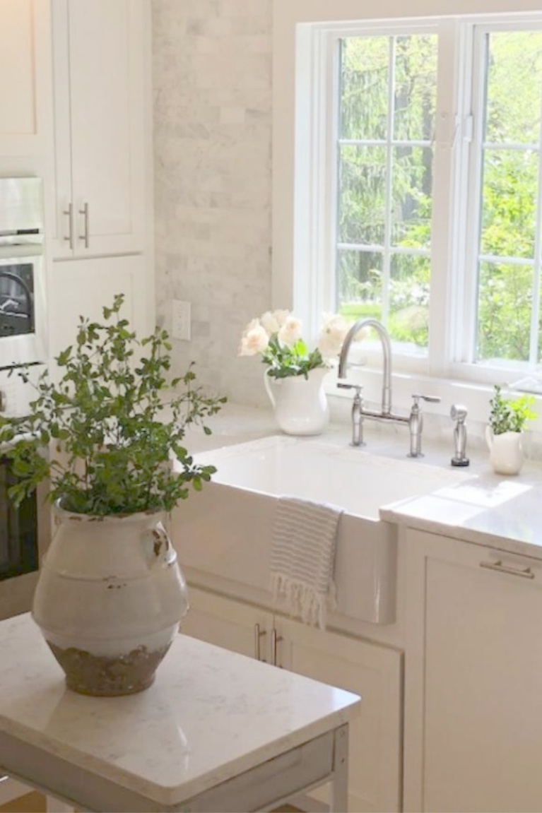 Serene white Shaker kitchen with fireclay farm sink and vintage work cart. Viatera Minuet quartz on counters. #hellolovelystudio #kitchendesign #serenedecor #viatera #minuet #farmsink #reinhard