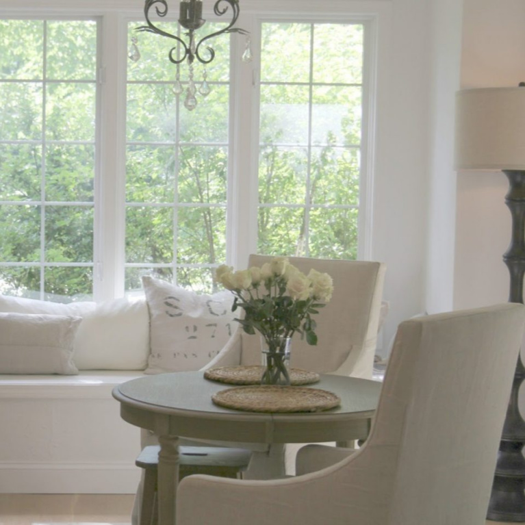 Window seat with European inspired pillows and Belgian linen slipcovered dining chairs in a breakfast area of a French country kitchen - Hello Lovely Studio. #frenchcountry #kitchendesign #breakfastroom #belgianlinen #windowseat #serenedecor