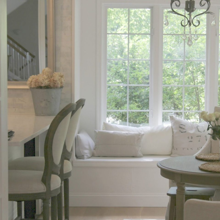 Window seat with European inspired pillows and Belgian linen slipcovered dining chairs in a breakfast area of a French country kitchen - Hello Lovely Studio. Find a Soft, Ethereal European Country Kitchen Mood to Inspire Now!
