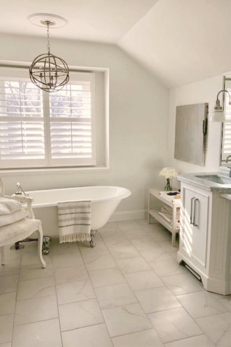 Serene white French country bathroom with vintage clawfoot tub and calacatta look porcelain tile. #hellolovelystudio #whitebathrooms #bathroomdesign #frenchcountry #clawfoottub