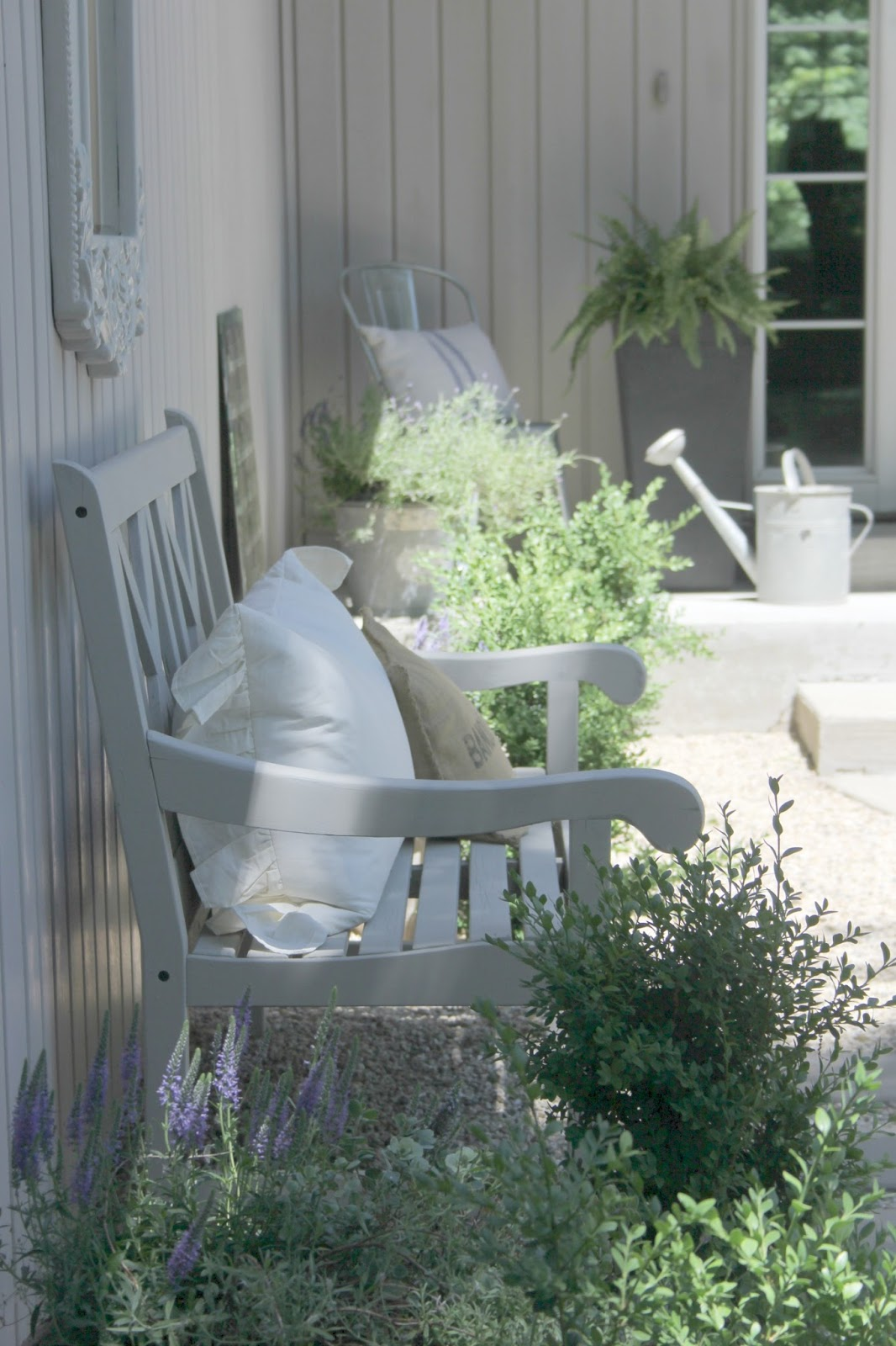 French farmhouse inspired courtyard with pea gravel, wood furniture, and vintage galvanized buckets. #hellolovelystudio #gardens #courtyards #frenchfarmhouse #peagravel #outdoorfurniture #outdoordecor