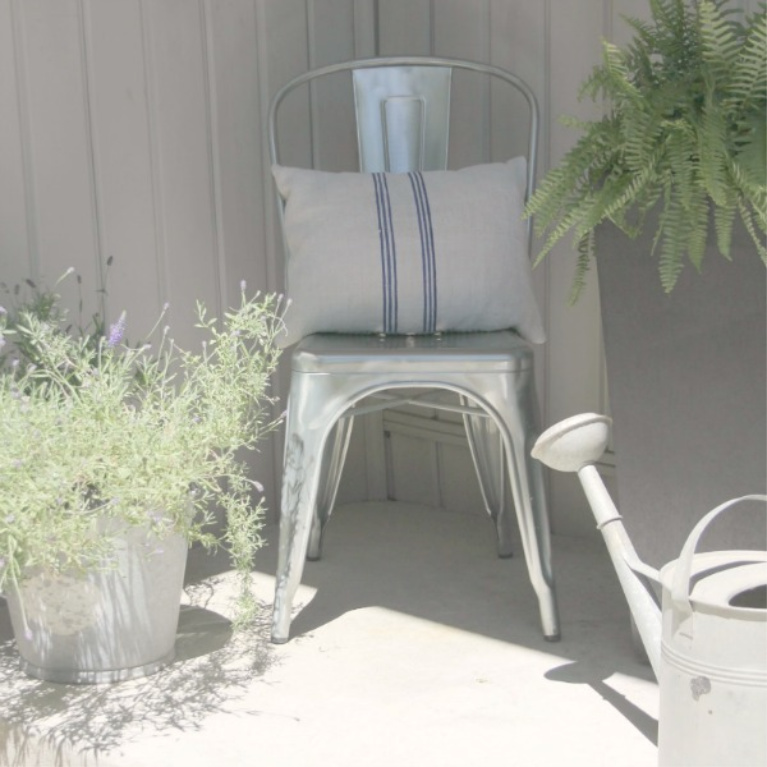 Industrial farmhouse metal chair with a grainsack cushion on my front porch with vintage watering can. #hellolovelystudio #frenchfarmhouse #metalchair #vintagestyle #wateringcan #outdoordecor