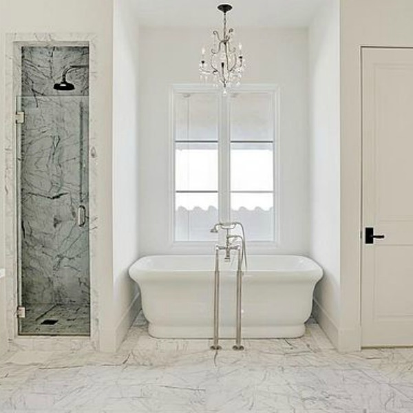 Oh the unforgettable timeless design of a luxurious white bathroom with soaking tub in a French home on Berthea in Houston. #interiordesign #luxuryhome #Europeanstyle #whitedecor