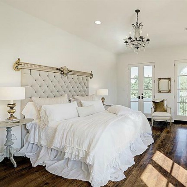 Beautiful all white French country bedroom with tufted velvet headboard and warm wood floors. See more elegant white country interiors in this story!