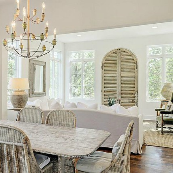 Modern French country style in a white living room and dining room with rustic wood accents and antiques. Come see more white country interiors and score tips for stealing the look.