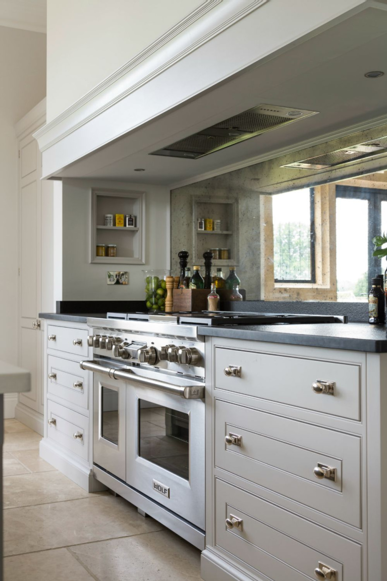 Cornforth White by Farrow & Ball is the paint color on these glorious bespoke kitchen cabinets flanking a range with antiqued mirror backsplash - Humphrey Munson. #paintcolors #cornforthwhtie #farrowandball #kitchencabinets