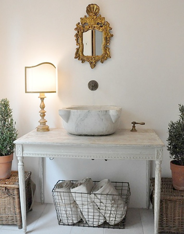 When a rustic French farmhouse powder room with repurposed antique table and vessel sink is this gorgeous, who would want to leave? Design by Brooke Giannetti. #europeancountry #oldworld #bathroom