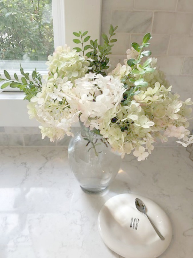 A mix of whites in my timelessly tranquil kitchen with European country decor, Viatera Minuet quartz, and Belgian linen - Hello Lovely Studio. COME SEE Timeless Kitchen Design Ideas and Decor to Freshen Your Traditional, Farmhouse, as well as French Country Kitchen.