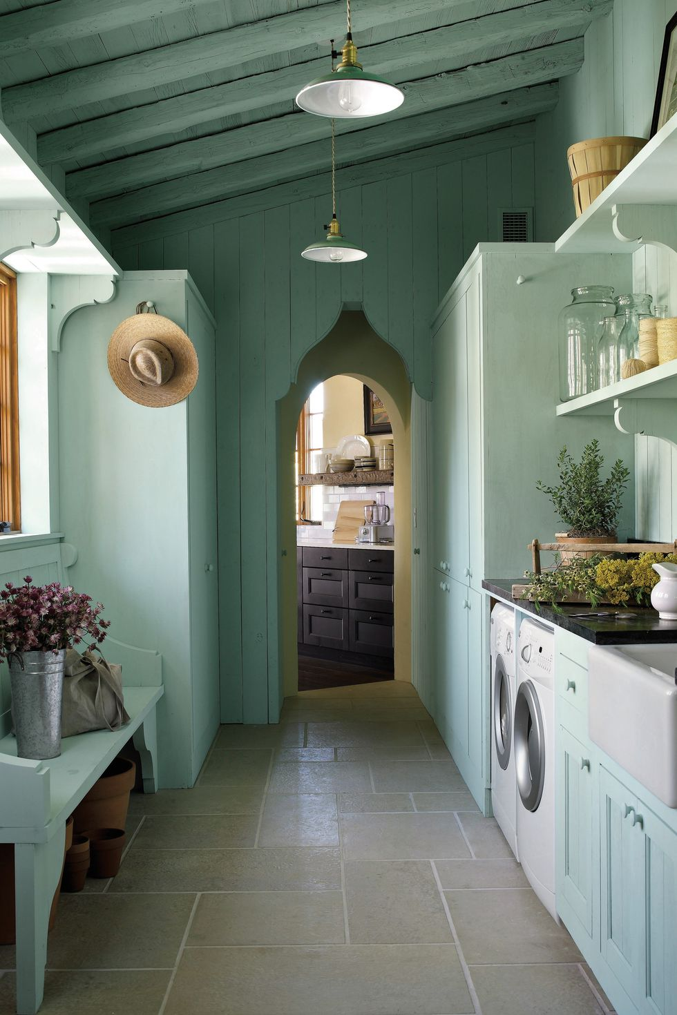 Breathtaking architecture and green color in a laundry room by architect Michael Imber - come enjoy more Dreamy Laundry Room Inspiration to Re-imagine a Timeless Tranquil Design!