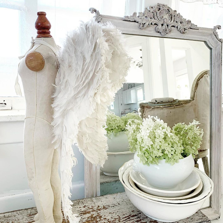 Serene and breathtaking French Nordic white child's angel wings styled in a vignette with antique mirror and ironstone - My Petite Maison.