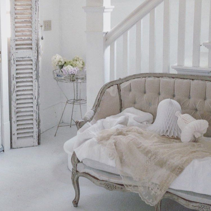 All white French Nordic decor, antiques, and interior design style in this breathtaking cottage with tufted French settee, crepe paper bells, and distressed shutter - My Petite Maison.