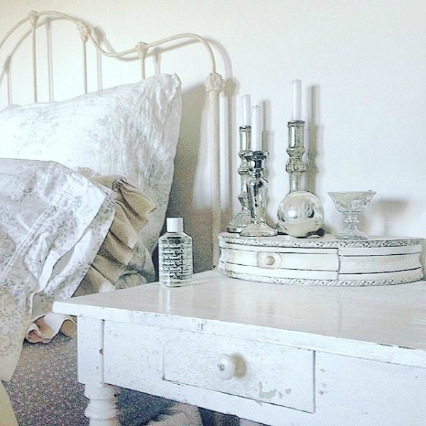 White on white Scandi style bedroom with vintage bedside table and metal bed feels calm and unfussy. See even more quiet, tone on tone, white country interiors in this story.