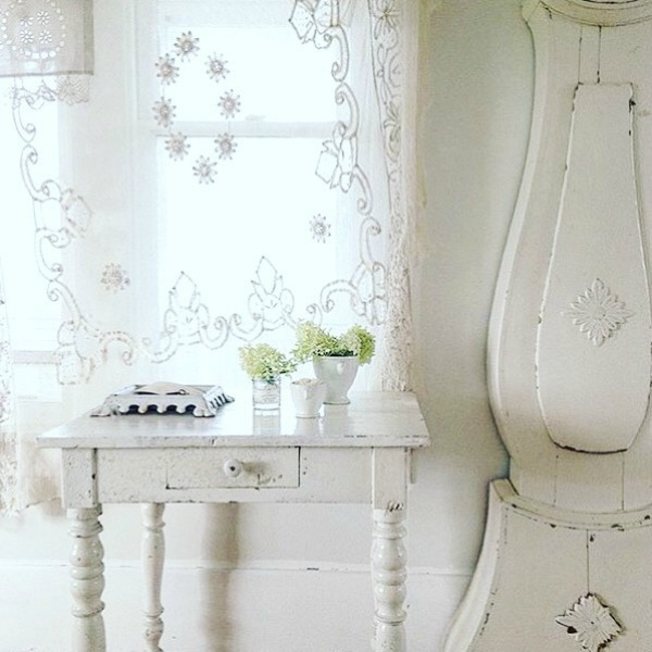 All white decor, a Swedish Mora clock, lace curtain panel, and a vintage painted table add up to French Nordic bliss from My Petite Maison.