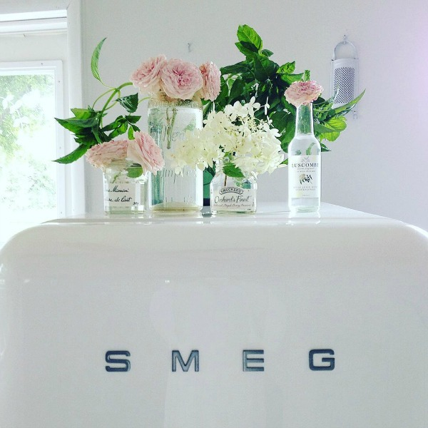 White Smeg refrigerator topped with lovely vintage glass bottles as vases for pink blooms - My Petite Maison.